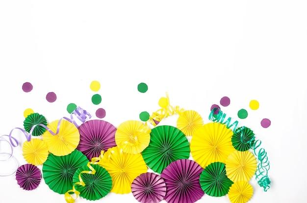 Farbiges papierkonfetti, karnevalsmaske und farbiger serpentin auf gelbem grund