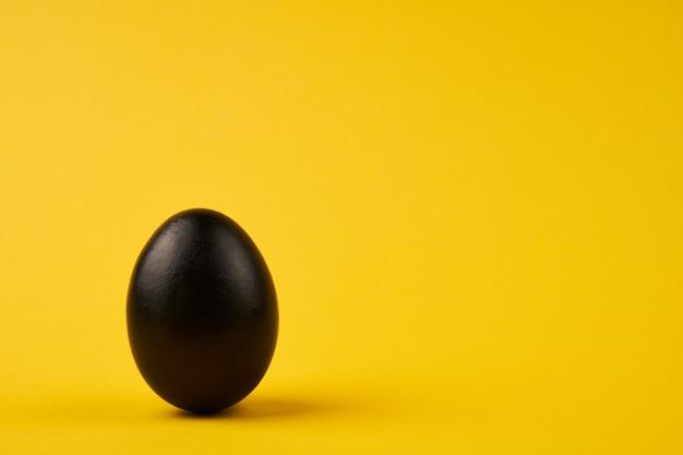 Farbiges schwarzes osterei auf hellgelbem hintergrund