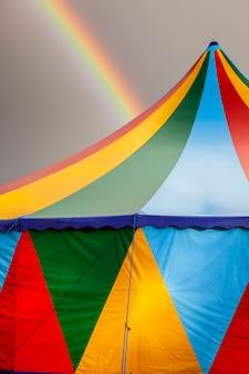 Farbiges zirkuszelt an einem regnerischen tag mit einem regenbogen am himmel