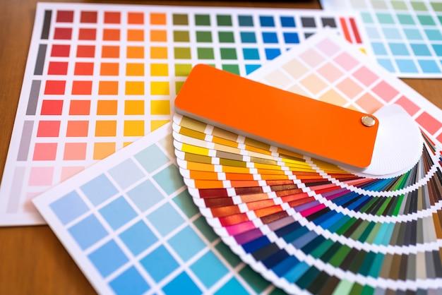 Farbmuster von den grafikdesignern, die auf schreibtischtabelle sich setzen.