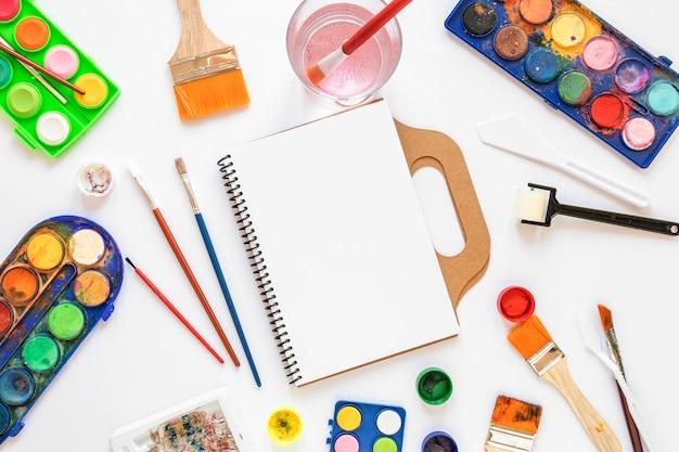 Farbpalette in kisten und leerem notizbuch