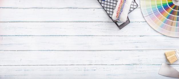 Farbpalette zum malen mit walzen-palettenmesser und sichter auf einem holztisch - ansicht von oben.