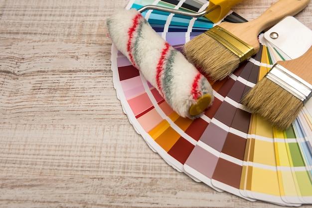 Farbpalettenführung und pinselrolle auf holzplatte