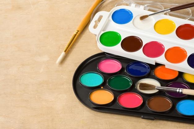 Farbpinsel und malerpalette auf hölzernem hintergrund