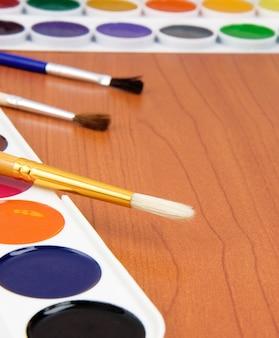 Farbpinsel und malerpalette auf holztisch