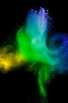 Farbpulver-explosionswolke auf schwarzem hintergrund. bewegung der farbstaubpartikel einfrieren.