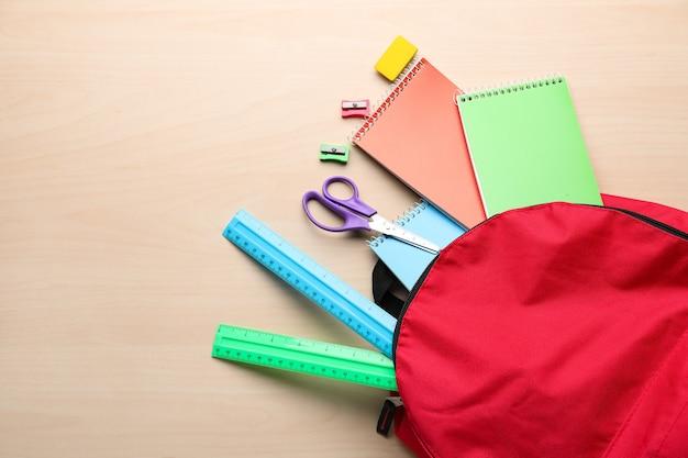 Farbrucksack mit schulbriefpapier auf dem tisch