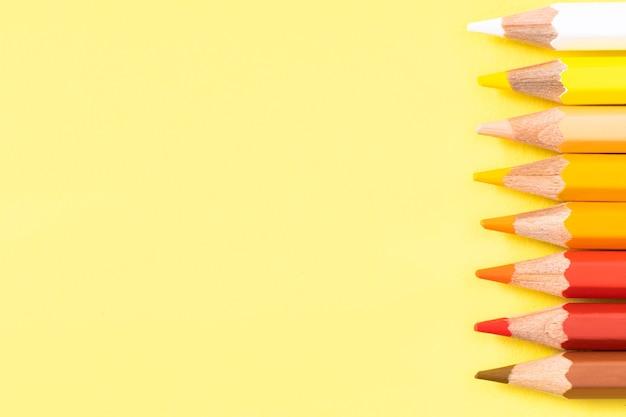 Farbstift auf gelbem hintergrund. platz für text. ansicht von oben