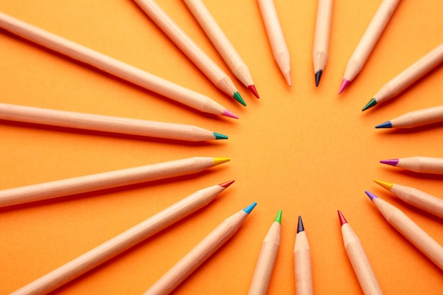 Farbstifte auf dem orangefarbenen hintergrund