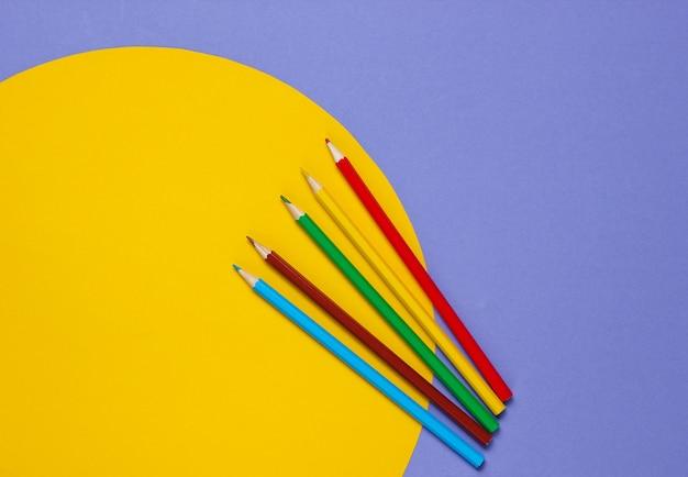 Farbstifte auf einem purpur mit einem gelben kreis