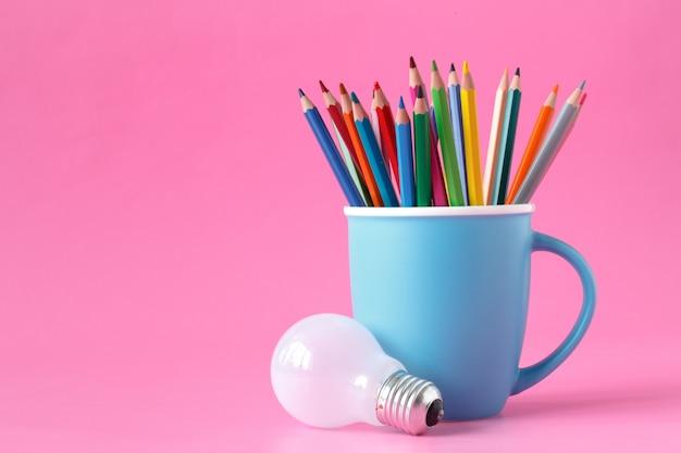 Farbstifte auf einer tasse und einer glühbirne
