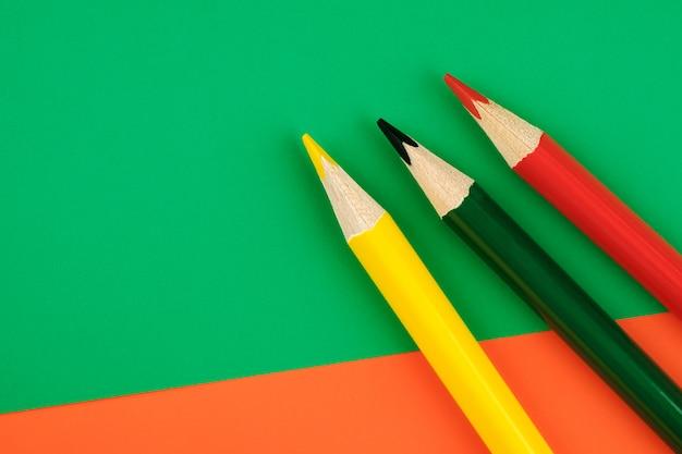 Farbstifte auf farbigem hintergrund. minimalistisches kreatives konzept
