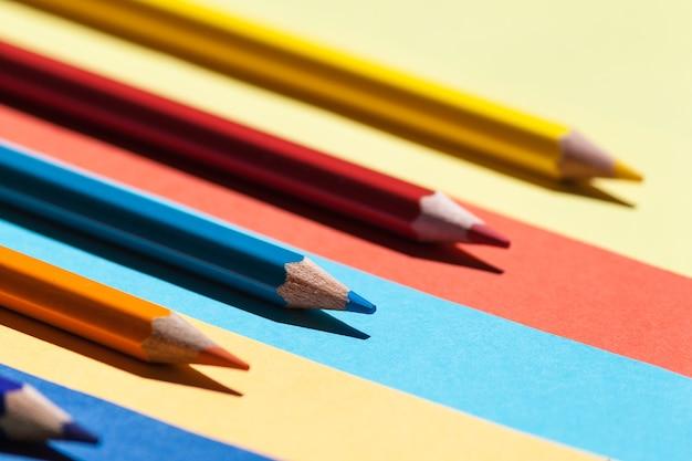 Farbstifte auf farbigem hintergrund. zurück zur schule, anordnungskonzept.