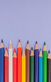 Farbstifte auf violettem hintergrund für projekte und ankündigungen