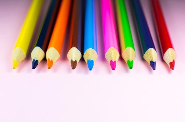 Farbstifte, die auf rosa hintergrund liegen. nahaufnahme. zurück zum schulkonzept. buntes kunststudium und malprozess. zeichnen mit bleistiften. platz für postkartenwunsch kopieren.