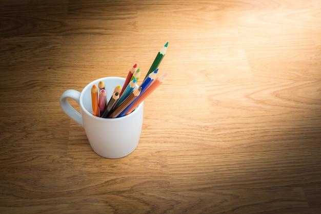 Farbstifte in der weißen kaffeetasse