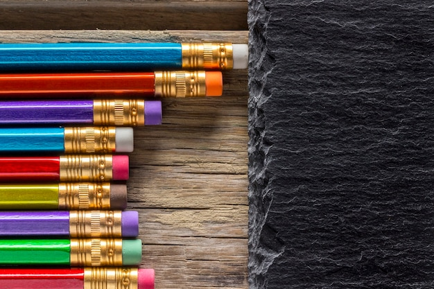 Farbstifte mit radiergummis und leerer schiefertafel