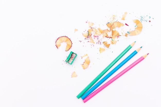 Farbstifte und bleistiftspitzer auf weißem hintergrund