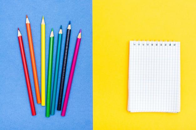 Farbstifte und ein notizblock auf zwei farben