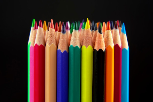Farbstifte zum zeichnen auf einem dunklen hintergrund. bildung und kreativität. freizeit und kunst