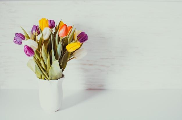Farbtulpen in einer weißen vase. frühlingskonzept mit kopierraum