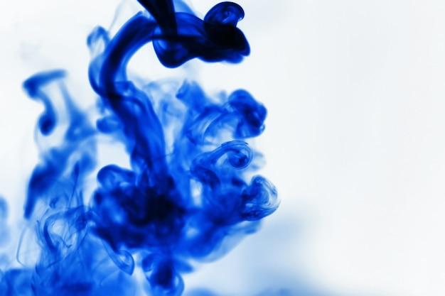 Farbtupfer im wasser. die auflösung des farbstoffs in wasser. wasserverschmutzung. konzeptkunst kreativität.
