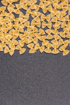 Farfalle italienische pasta. fliege pasta auf grauem raum. vertikaler rahmen, kopierraum
