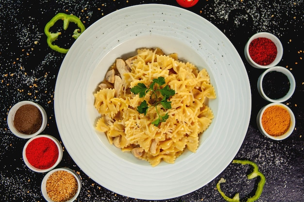 Farfalle mit hähnchen und champignons, garniert mit geriebenem parmesan