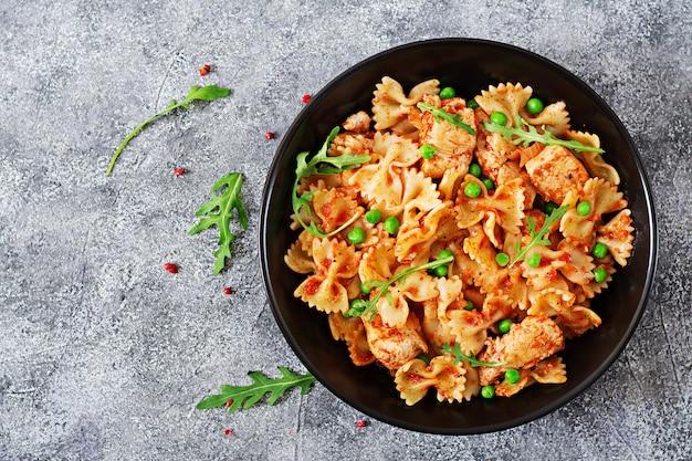 Farfalle-nudeln mit hähnchenfilet, tomatensauce und grünen erbsen. speisekarte. draufsicht. abendessen.