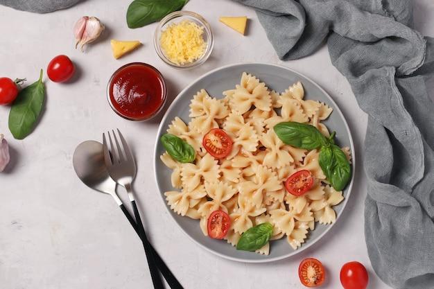 Farfalle-nudeln mit kirschtomaten, tomatensauce und basilikum auf grauem hintergrund. von oben betrachten