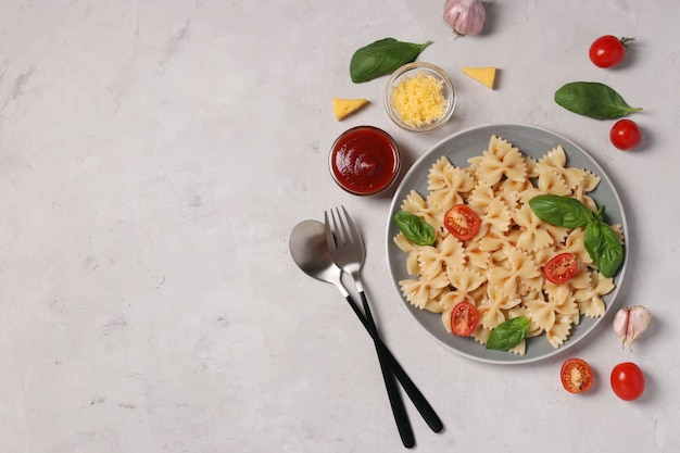 Farfalle-nudeln mit kirschtomaten, tomatensauce und basilikum auf weißem hintergrund,