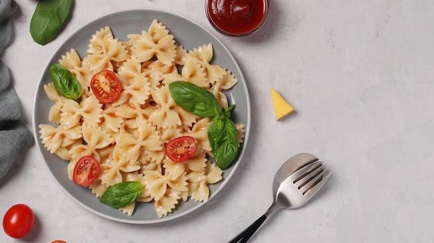 Farfalle-nudeln mit kirschtomaten, tomatensauce und basilikum auf weißer oberfläche, draufsicht, platz für text