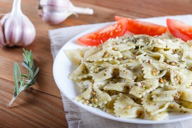 Farfalle-nudeln mit pestosoße, tomaten und käse auf einer leinentischdecke auf braun