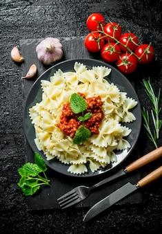 Farfalle nudeln mit tomaten, rosmarin und knoblauch. auf schwarzem rustikalem hintergrund