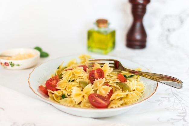 Farfalle-nudeln mit tomaten- und olivenscheiben auf keramischer platte