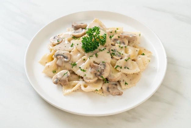 Farfalle-nudeln mit weißer champignon-sahne-sauce - italienische küche