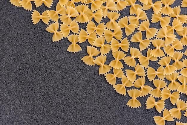 Farfalle oder fliege pasta auf schwarzem hintergrund. hintergrund kochen. italienische küche. speicherplatz kopieren. vorlage. attrappe, lehrmodell, simulation