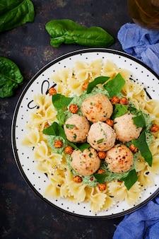 Farfalle pasta mit fleischbällchen und spinatsauce mit gebratenen kichererbsen