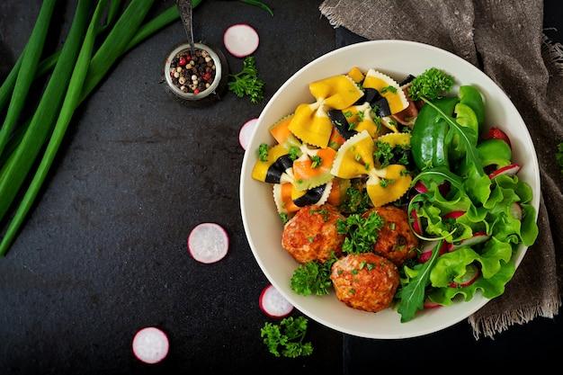 Farfalle-teigwaren-hartweizen mit gebackenen fleischklöschen des hühnerfilets in der tomatensauce