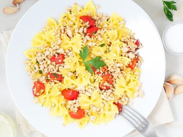 Farfalle-teigwaren mit tomaten, chiken fleisch, petersilie auf weißem steinhintergrund, kalorienarme diät