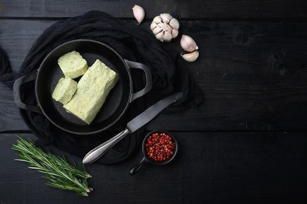 Farm butter mit einem kraut für sandwiches und steak-set, auf schwarzem holztischhintergrund, mit kopienraum für text