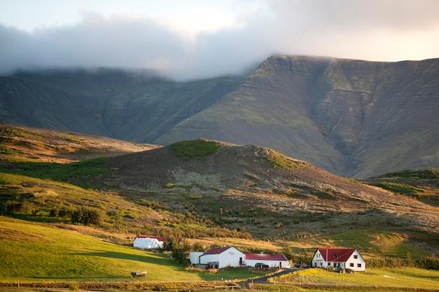 Farm im schatten eines wolkigen berges