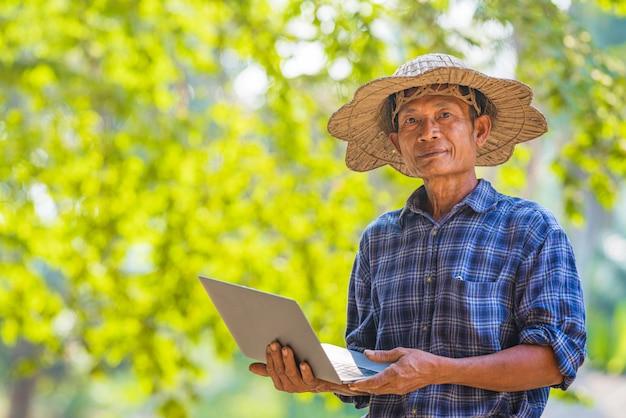 Farmer asian mit smartphone und laptop, business- und technologiekonzept