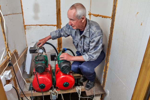 Farmer führt die wartung der haushalts-trinkwasserleitung nach hause.