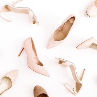 Fashion-blog-look. blassrosa frauenschuhe mit hohen absätzen auf weißem hintergrund. flache lage, ansicht von oben