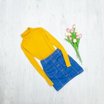Fashion-konzept. gelber rollkragenpullover, blauer rock und rosa tulpen. holz hintergrund