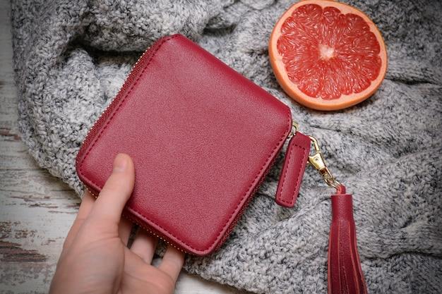 Fashion-konzept. kleiner roter geldbeutel in einer weiblichen hand