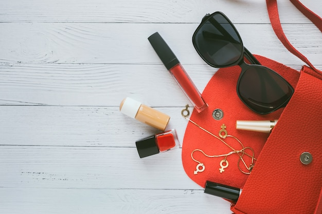 Fashion-konzept. rote handtasche, kosmetikprodukte, sonnenbrille, ohrringe.