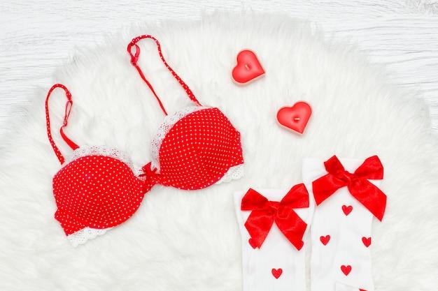 Fashion-konzept. roter bh und weiße strümpfe mit schleifen, kerzen in form des herzens. weißes fell