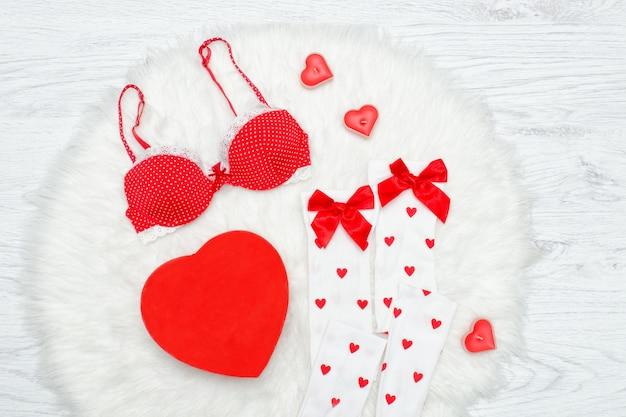 Fashion-konzept. roter bh, weiße strümpfe und box in form von herzen. weißes fell